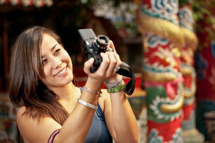 Asian woman taking a photo with a camera.