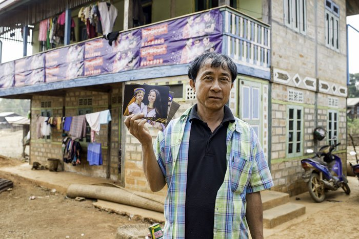 Kayan man in a village in Myanmar with a photo of his daughter and grand daughter