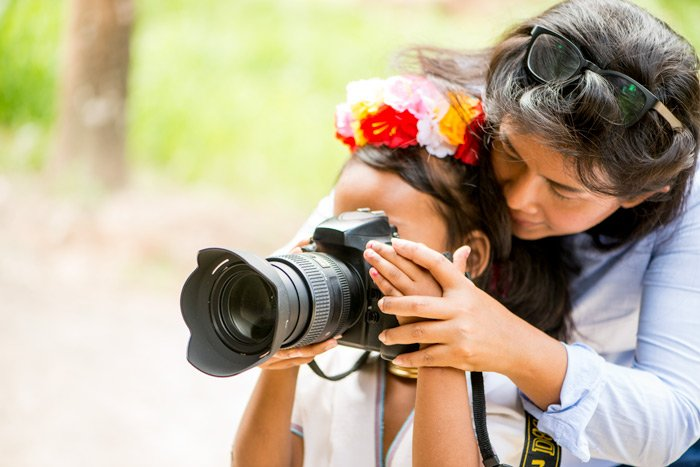 woman teaching a child to use a dslr camera