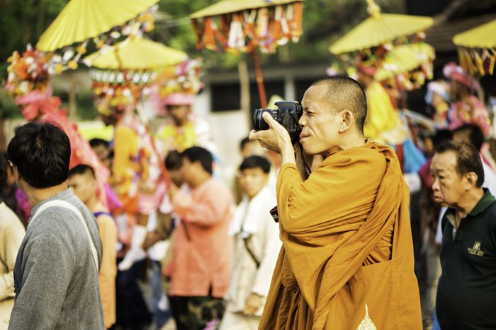 Buddhist monk taking a photo during the Poi Sang Long festival in Mae Hong Son, Thailand.