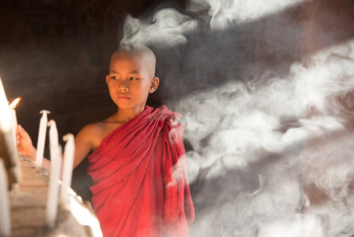 novice monk lights candles and is surround by smoke as he poses for photographers.