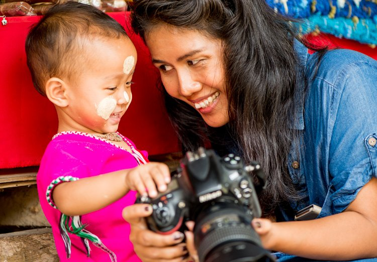 Thai woman and Kayan child with a camera