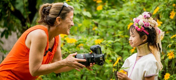 Woman photographer shows a girl her photo on the comaera montior during a 5 day photography workshop in Chiang Mai, Thailand