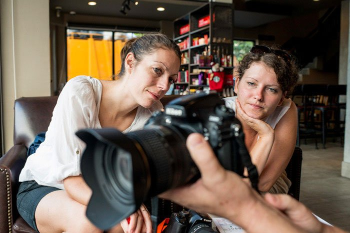 Two women on a photography workshop being shown the functions of a DSLR camera