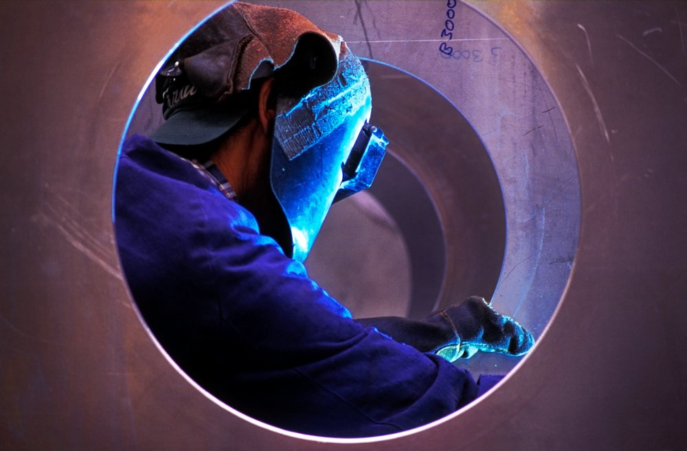 Aluminium welder wearing protective clothing working.