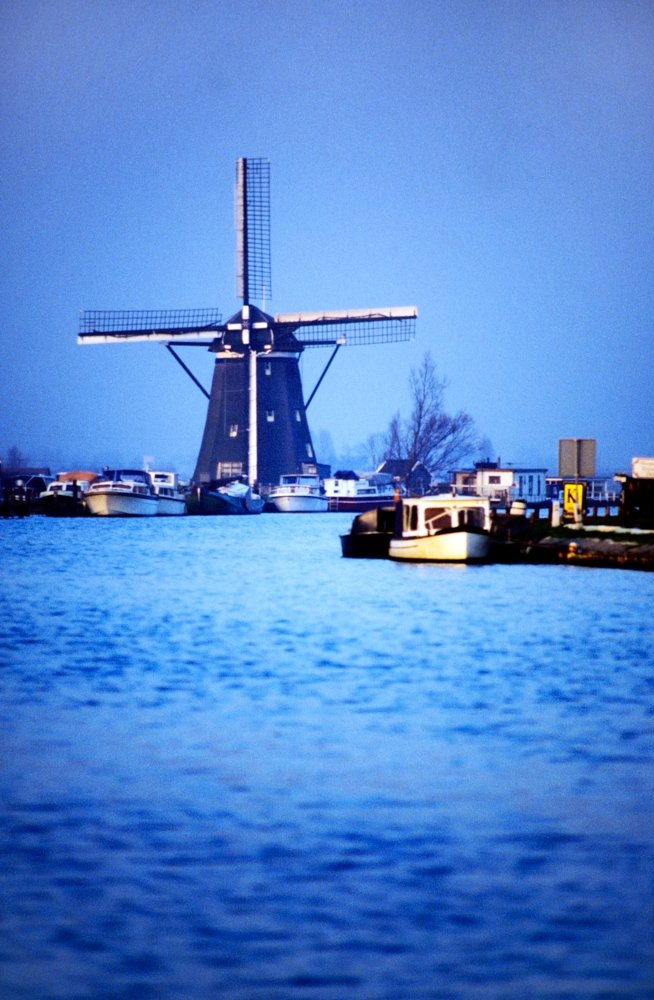 Old windmill near river in Holland.