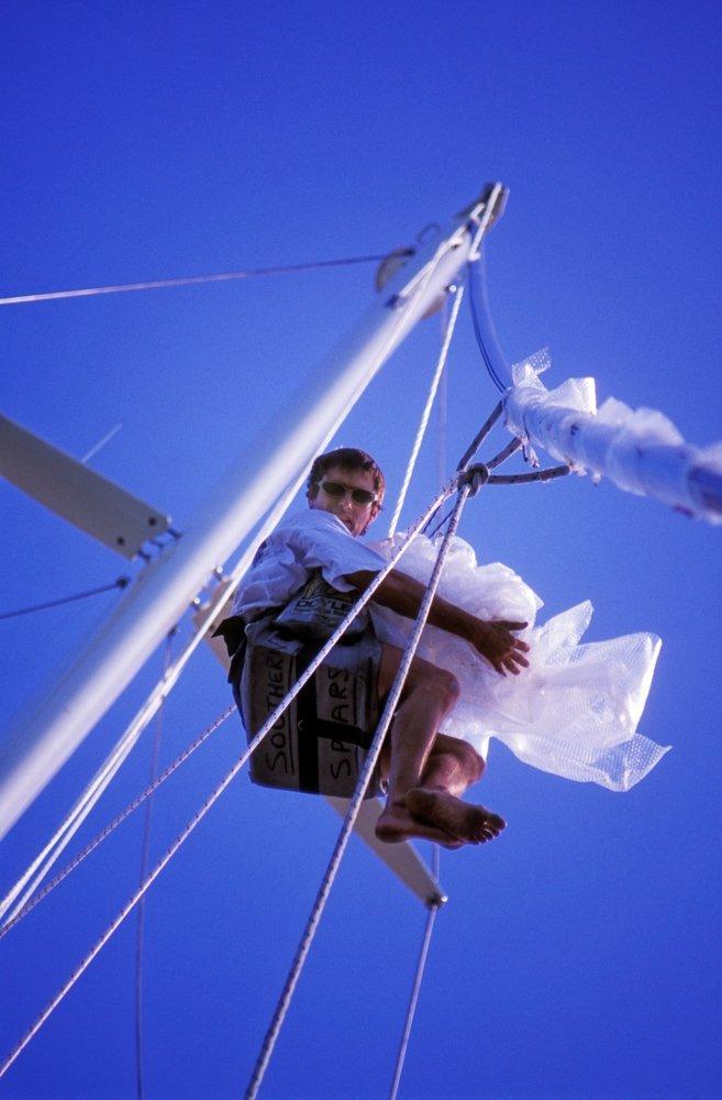 Yacht crew member up mast