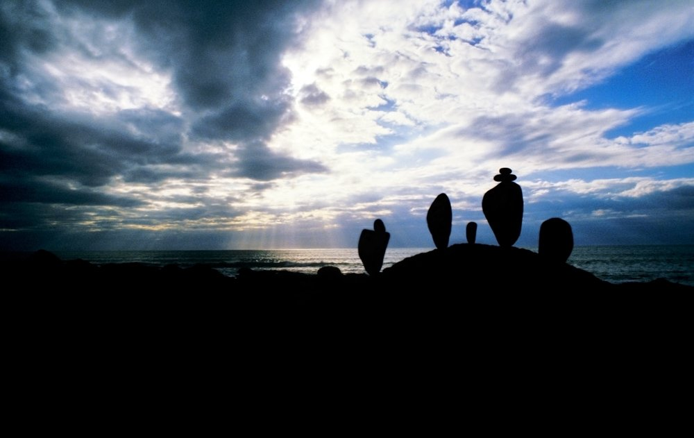Stacked rocks silhouetted against a moody sky
